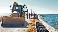 На дамбе сакского солёного озера кипит работа